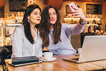 Two young women sit in a cafe at a table in front of a laptop and do selfie on a smartphone. Meeting two friends, colleagues have lunch in a cafe, break during work. Girls blogging, working, learning.