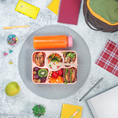 Open lunch box with healthy food on the grey background with school backpack