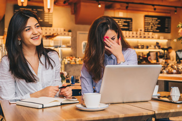 Two young happy women are sitting in cafe at table, using laptop and laughing. On table paper notebook and cup of coffee. Girls are blogging, working, studying online. Online marketing, education.