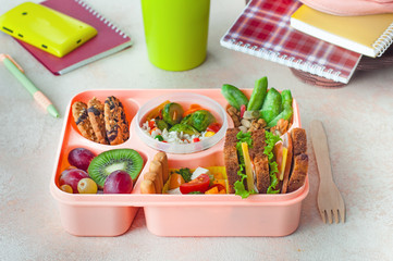 Open lunch box with healthy lunch on office table near backpack and mug