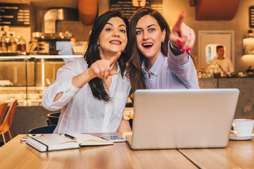 Two young business women are sitting in a cafe at a table in front of a laptop. Girls with joyful surprise point fingers at what they see outside the window. Girls look surprised, delighted, joyful.