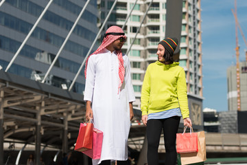 Arabic man and tourist woman shopping in city