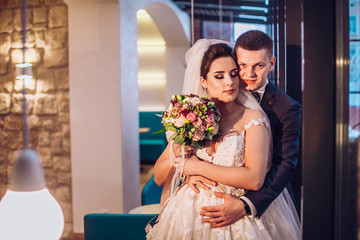 Gorgeous wedding couple in the cozy little cafe in the old town. warm light illuminates