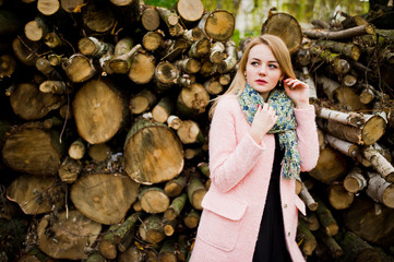 Young blonde girl at pink coat posed against wooden stumps background.