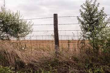 Old wooden post with three strands of barbed wire and metal fencing.