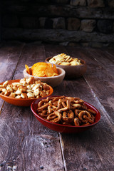 Salty snacks. Pretzels, chips, crackers in wooden bowls