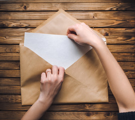 Female hands open a large brown envelope and take out a letter from it. Wooden background.