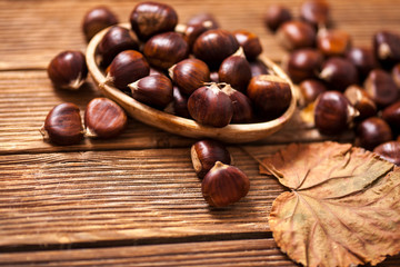Ripe chestnuts in a frying pan on old wooden table close up with copy space. Roasted Chestnuts for Christmas'n