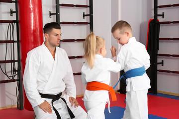 Male karate instructor training little children in dojo