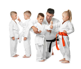 Little children with instructor practicing karate on white background