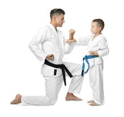 Little child with instructor practicing karate on white background