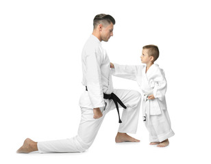 Little boy with instructor practicing karate on white background