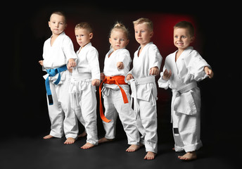 Little children practicing karate on dark background
