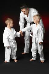 Little children with instructor practicing karate on dark background
