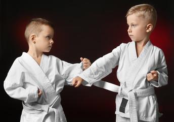 Little children practicing karate on dark background