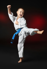 Little boy practicing karate on dark background