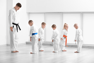 Photo sur Plexiglas Combat Little children and instructor performing ritual bow prior to practicing karate in dojo