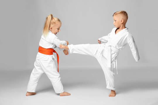 Little children practicing karate on light background