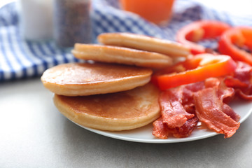 Plate with yummy pancakes, pepper and fried bacon on table