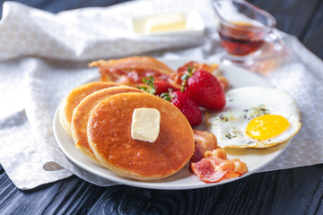 Plate with yummy pancakes, strawberry, fried egg and bacon on wooden table
