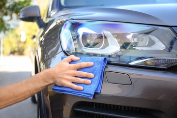 Man cleaning car headlight with rag outdoors Wall mural
