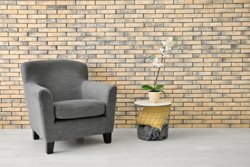 Comfortable armchair and table near brick wall
