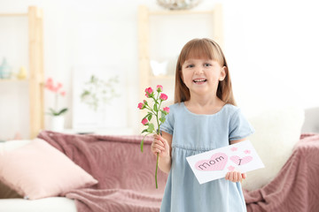 Little girl holding greeting card and flower for Mother's day at home