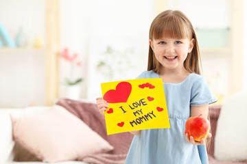 Little girl holding greeting card and apple for Mother's day at home