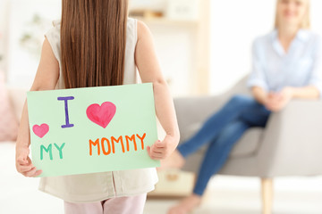 Little girl hiding greeting card for Mother's Day behind her back at home