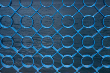 Blue fence circles and x patterns with lake ripples in background
