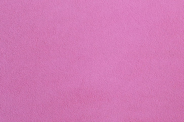 The blanket of furry pink fleece fabric. A background texture of light pink soft plush fleece material