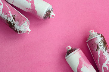 Some used pink aerosol spray cans with paint drips lies on a blanket of soft and furry light pink fleece fabric. Classic female design color. Graffiti hooliganism concept