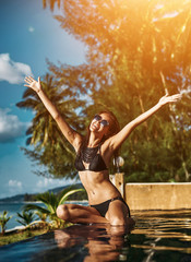 Lifestyle portrait of attractive girl having fun and party on a tropical beach