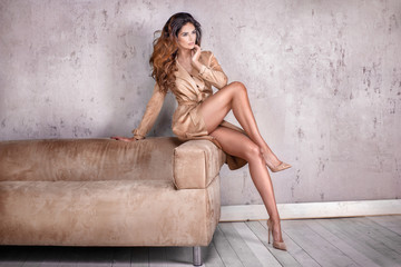 Beautiful lady with long curly hairstyle and slim legs posing.