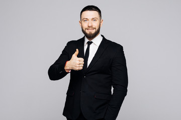 Portrait of excited man in formal wear giving thumbs-up against gray background