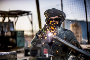 Man welding in the desert..