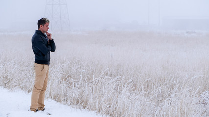 Farmer with sad face, bad mood stands at wheat field covered in snow, winter foggy day. 16x9 wide screen, banner size