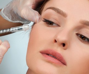 Woman is getting filler injection in cheeks. Anti-aging treatment and face lift. Cosmetic Treatment and Plastic Surgery