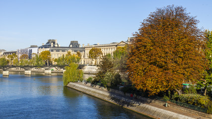 PARIS, FRANCE, on October 30, 2017. Autumn city landscape. The sun lights the river Seine, the turned yellow trees ashore and beautiful houses which make an architectural complex of the embankment