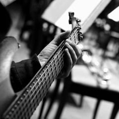 Hand of the musician on strings of a guitar in black and white tones
