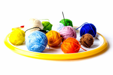 Woolen balls of yarn, tambour and embroidery. Subjects for needlework. Balls of yarn and knitting needles. Embroidery frame, thread reels for embroidery.