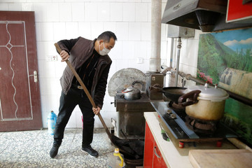 A man shovels coal into a tray next to an oven he uses to heat his home in his kitchen in the village of Heqiaoxiang