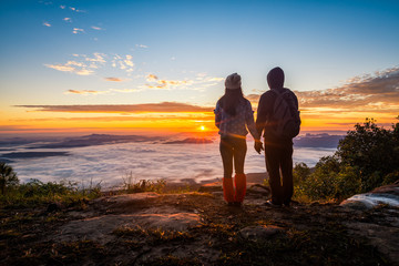 Young couple watching the sun rise from top of mountain