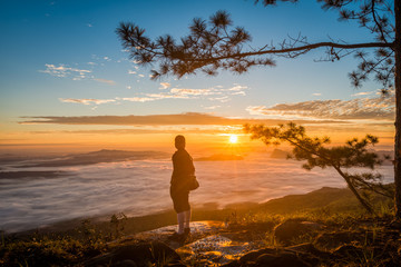 Young man watching the sun rise from top of mountain