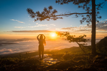 Young woman watching the sun rise from top of mountain