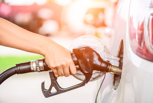 Closeup of woman  hand holding a fuel pump at a station.