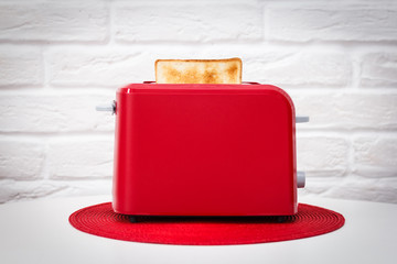 Red toaster with toasted bread for breakfast inside. Red table napkin. White table. White brick wall.