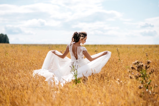 A beautiful bride in wedding dress is dancing alone in a field of wheat. View from the back