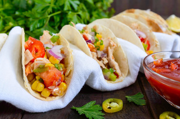Mexican tacos with meat, corn, tomatoes, sweet pepper, red onions in a wheat tortilla with a spicy tomato sauce.