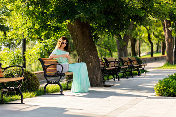 Young beautiful woman in a light green pastel long dress is sitting on a park bench and is looking at a mobile phone.